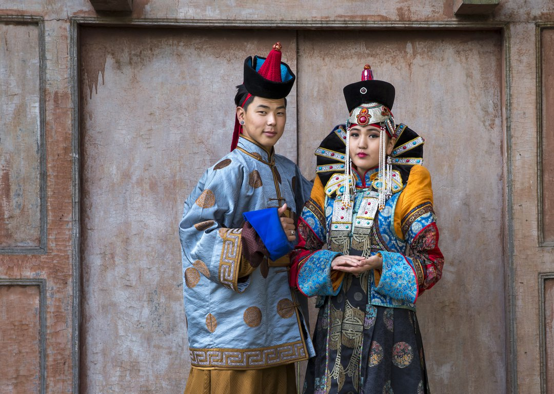MONGOLIAN COUPLE IN TRADITIONAL OUTFIT NEAR OLD TEMPLE IN ULAANBAATAR image